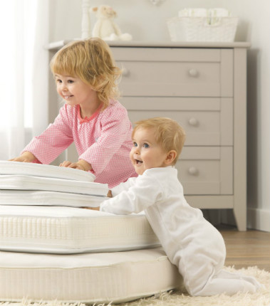 two little children playing on mothercare mattresses